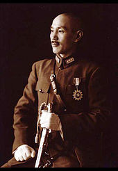 A Chinese man in military uniform, smiling and looking towards the left. He holds a sword in his left hand and has a medal in shape of a sun on his chest.