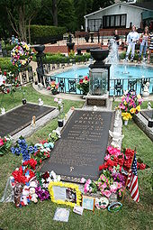 "A long, ground-level gravestone reads ""Elvis Aaron Presley"", followed by the singer's dates, the names of his parents and daughter, and several paragraphs of smaller text. It is surrounded by flowers, a small American flag, and other offerings. Similar grave markers are visible on either side. In the background is a small round pool, with a low decorative metal fence and several fountains."