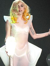A blond female, holding a lighted-bulb stick. She has yellow curls and wears a translucent white dress.