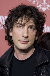 Photograph of man's head. He has black, curly, mussed hair, and a piercing expression.