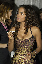 Upper body shot of Berry dressed in brown and gold evening gown and holding an autograph pen.