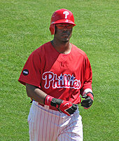 "A dark-skinned man in a red baseball jersey and red left-handed batting helmet walks on a baseball field; he appears to be in his mid-twenties. His jersey reads ""Phillies"" in white and red script, with two blue starts dotting the ""i""s."