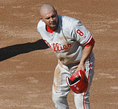"A man in a gray baseball jersey having just removed his red batting helmet at first base. His jersey reads ""Phillies"" in white and red script and has a number ""8"" on the left sleeve."