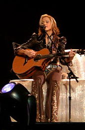 A blond woman sitting on a block of hay. She is playing a guitar and singing in front of a standing microphone. She has short hair and wears grey colored cowboy clothes.