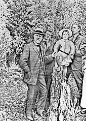 Faded, grainy image of three men in the outdoors, holding up a boy. The man on the left has a short white beard and mustache, a hat, and a three-piece suit.
