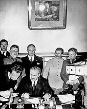 Soviet Foreign Minister Vyacheslav Molotov signs the Molotov-Ribbentrop Pact. Behind him stand German Foreign Minister Joachim von Ribbentrop and Soviet Premier Joseph Stalin.