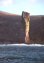 A tall perpendicular stack of brown rock stands in the sunlight in front of a shore with high cliffs that lie in the shadows.
