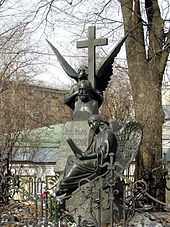 A statue of a winged angel holding a large stone cross over the bust of a balding middle-aged man.