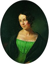 Portrait of a young lady, over a black background. She is wearing a green dress, over a black coat. She is looking to the left, somewhat smiling.