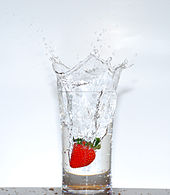 a glass of transparent water sitting on a wooden table