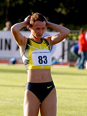Yelena Slesarenko with her hands on her head, wearing a yellow and blue top and blue running briefs