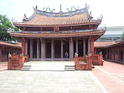 A religious temple. A one meter high stair leads to the ground floor. Two large pillars and six smaller ones supports a red tiled roof.