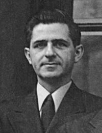 """Black and White head and shoulder shot of 30's white male with thick black hair, and a three piece suit from the 1940s."""