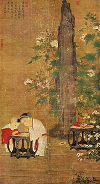 A portrait oriented painting depicting two young children, a boy and a slightly older girl, playing with figurines on a table in a garden. Behind them is a tall rock flanked by branches of a flowering tree.
