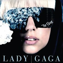 "The face of a blond woman. She is wearing black glasses. The right side of the glasses is covered by blue crystals. On the bottom of the left side of the glasses, the word ""The Fame"" is written in white."