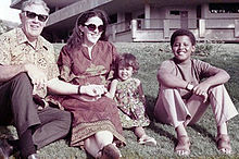 A young boy possibly in his early teens, a younger girl (about age 5), a grown woman and an elderly man, sit on a lawn wearing contemporary circa-1970 attire. The adults wear sunglasses and the boy wears sandals.