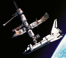 A cluster of cylindrical modules with projecting feathery solar arrays and a space shuttle docked to the lower module. In the background is the blackness of space, and, in the lower right corner, Earth.