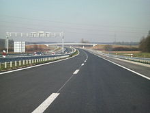 A view of four lane motorway with a central reservation, taken from a carriageway level. Back side of a gantry carrying variable traffic signs is visible on the left hand side carriageway.