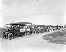 "A black and white photograph of a line of at least seven open-air buses filled with potential real estate investors, showing banners that read ""HI-A-LE-AH"", stopped on white dirt roads surrounded by lawns in undeveloped neighborhoods; some houses in the background"