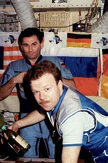 Two men seen in front of a wall featuring a number of switches and dials and covered by large American, Russian and German flags. The men are wearing blue jumpsuits, and two ventilation hoses are visible at the top of the image.