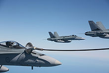 Three grey jet fighters in formation. The aircraft closest to the camera has a hose attached to it.
