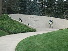 "An arching stone wall is set into a small grass-covered hillside. The wall is engraved thus: ""Lives Committed to God, Country, and Love"", with two names engraved underneath, reading ""Gerald R. Ford, 1913–2006"" and ""Elizabeth Bloomer Ford, 1919–2011 "". Two flowered wreaths are placed beside the names on stands."