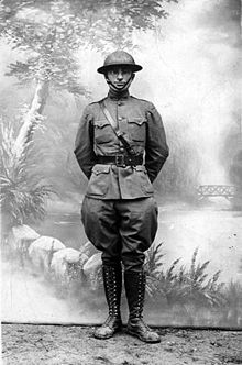 Man in military uniform with shoulder and waist belt with helmet