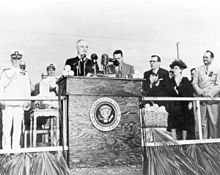 A black and white photograph of President Harry Truman standing at a podium bearing the presidential seal on a stage with people behind him applauding