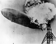 A black and white photograph of an airship near a mooring mast exploding at the rear.