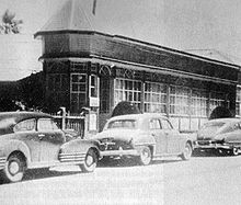 Black and white photo of a building with cars parked in front