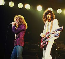 A colour photograph of Robert Plant with microphone and Jimmy Page with a double necked guitar performing onstage.