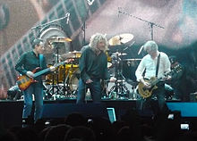A colour photograph of John Paul Jones, Robert Plant and Jimmy Page performing onstage, with Jason Bonham partially visible on drums in the background