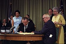 Two men at a desk with a document one is signing with their wives standing behind them