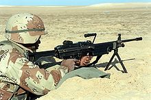 A U.S. Marine with an M249 SAW on its bipod manning a foxhole during the 1991 Gulf War