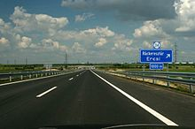 A view of the motorway carriageway from a car, showing two traffic lanes and traffic signs indicating approach to an exit.