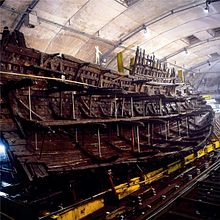 A diagonal section of a wooden ship resting upright on a yellow steel frame inside a building with bare, drab walls and sprinkler systems in the ceiling