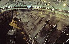 A diagonal section of a wooden ship is lying on its side steel frame at an angle, being sprayed with water from dozens of sprinklers