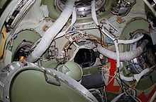 A view of the station's node module, with four open hatches visible. Each hatch is surrounded by a wide green ring, with the node walls coloured white. Numerous ventilation hoses and cables are visible passing between the hatches, and a gyrodyne and hatch cover are seen floating toward the lower left of the image.