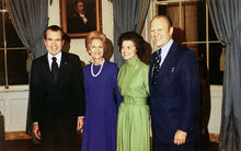 Two women are flanked by two men in suits, standing in a room of the White House.