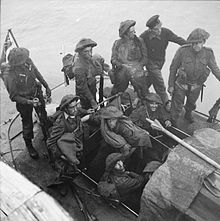 nine British soldiers and one sailor on a small boat at sea. A Union Jack flies from a mast at the rear
