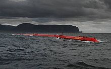 A long red tube lies in the water under dark, cloud-covered skies with black hills in the distance.