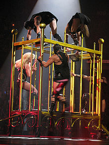 The right profile of a female blond performer. She is moving inside a giant golden cage. She is wearing a black corset with diamonds and fishnet stockings. Four leather-clad men seem to be chasing her.