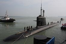A Scorpène class submarine at dock, half out of the water. People on top are mooring it, and a boat can be seen in the background