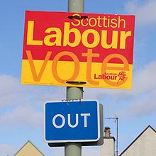 "A yellow, orange and red election sign reading ""Scottish Labour: Vote Scottish Labour"" attached to a lamppost above a road sign stating ""Out"""
