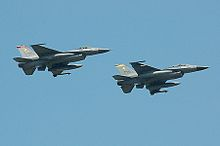 Two grey jet fighter aircraft over a blue sky