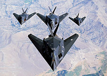 Look-down view of four black aircraft flying in formation, three of which fly behind and underneath the lead aircraft.