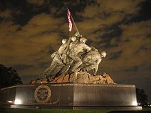 Color photo of the USMC War Memorial, a bronze statue of six men planting a flagpole with an American Flag into the ground.