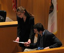 A woman and a man reading a document in a courtroom