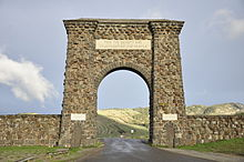 A large arch made of irregular-shaped natural stone over a road