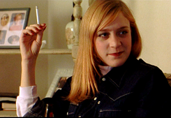 Photo of a young strawberry-blonde woman with a smile on her face; she is clad in a dark jean jacket and holding a cigarette.
